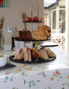 Afternoon tea at Gregynog Cafe: sandwiches, cakes, and other delights presented on a three-tiered cake stand