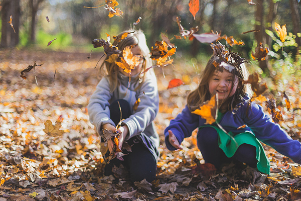 Image showing children playing outdoors with fallen leaves